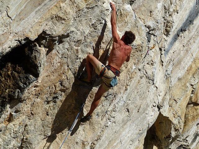 Photo d'un homme qui fait de l'escalade avec technicité